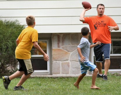 Playing catch with a football in a front yard on McLeans Station Road in Marlborough (PA) Township.